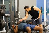 athlete african man in gym with personal fitness trainer