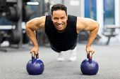healthy man doing pushup exercise with kettle bell in gym