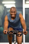 happy african man using stationary bicycle in a gym