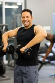 cheerful muscular man exercise with dumbbells
