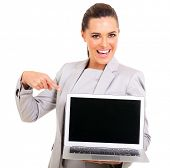 happy corporate worker pointing at laptop screen on white background