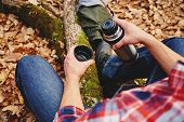 image of thermos  - Unrecognizable hiker man holding a cup of tea or coffee and thermos in autumn forest - JPG