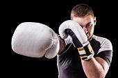 foto of kickboxing  - a young kickboxer or boxer isolated over a black background