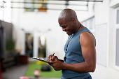 side view of happy young african american gym trainer writing on clipboard