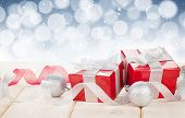 Christmas gift boxes and decor over wooden table with copy space