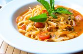 Tagliatelle pasta with tomato sauce and basil. Italian cuisine.