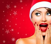 Christmas Woman. Beauty Model Girl in Santa Hat over holiday red Background. Funny Laughing Surprised Woman Portrait. Open Mouth. True Emotions. Red Lips and Manicure. Beautiful Holiday Makeup