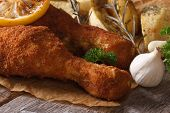 Fried Chicken Leg Dipped In Batter With Potatoes And Lemon