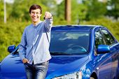 Happy young man in glasses standing in front of his new car and showing car key