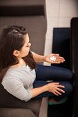 picture of home remedy  - Young woman looking at a bunch of pills in her hand while sitting at home - JPG