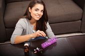 pic of home remedy  - Beautiful young woman sorting some of her pills on a pill organizer at home - JPG