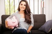 stock photo of money  - Cute Hispanic young woman saving money in a piggy bank and smiling - JPG