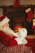 Santa claus holding piggy bank at christmas at home in the living room