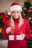 Smiling woman in santa hat opening a gift at hoem in the living room