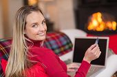 Smiling blonde shopping online with laptop at christmas at home in the living room