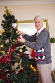 Senior man decorating the christmas tree at home in the living room