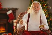 Santa holding glass of milk and plate with cookie at home in the living room