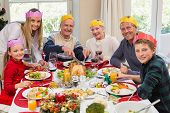 Grandfather in party hat carving chicken during dinner at home in the living room