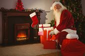 Cheerful santa delivering gifts at christmas eve at home in the living room