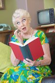 picture of tawdry  - One astonished senior female reading a book - JPG