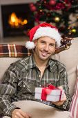 Smiling man in santa hat showing a gift at home in the living room