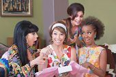 foto of risque  - Happy woman in hair band holding gift box with friends