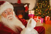 Smiling santa holding engagement ring at home in the living room