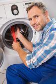 Handyman fixing a washing machine in the kitchen