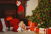 Santa claus napping on the rug near a christmas tree