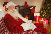 Smiling santa claus listening music at home in the living room