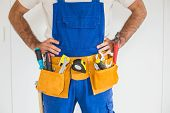 Handyman standing in tool belt in a new house