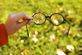 Glasses in hand on green grass background