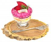 Russian herring salad in glass bowl, on wooden board, isolated on white