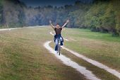 picture of dirt-bike  - Attractive young man riding bike on dirt road in forest - JPG