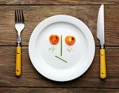Vegetable face on plate with knife and fork on wooden table