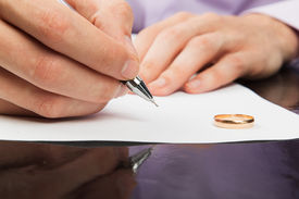 image of divorce-papers  - Closeup of male hand signing divorce papers - JPG