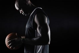 foto of balls  - Side view of fit young basketball player holding ball against black background with copy space - JPG