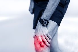 stock photo of muscle  - Knee pain runner leg and muscle pain running and training outdoors sport and jogging physical injuries when working out - JPG