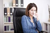 picture of bereavement  - Distressed attractive businesswoman sitting crying in the office wiping her eye with a tissue due to bereavement of failure at work - JPG