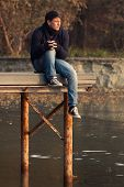 stock photo of pier a lake  - Young boy on a lake pier in a meditative calm scenery outdoors - JPG