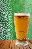 stock photo of ice crystal  - Frost beer glass against of ice crystals and drips green background taken closeup - JPG