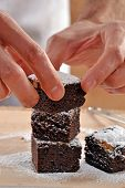pic of pastry chef  - Pastry chef hands preparing and slicing fresh chocolate brownies on cutting board - JPG