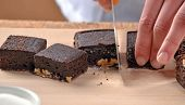 picture of pastry chef  - Pastry chef hands preparing and slicing fresh chocolate brownies on cutting board - JPG