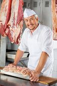 picture of slaughterhouse  - Portrait of confident mature butcher with chicken pieces on table in butchery - JPG