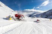 pic of grooming  - Trailing groomer grooming a ski run at ski resort on a sunny winter day - JPG
