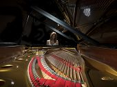 picture of grand piano  - Female pianist performing on a grand concert piano - JPG
