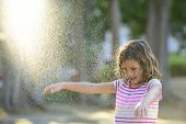 foto of dancing rain  - Happy smiling little girl outdoor in a sunny day enjoying the light rain - JPG