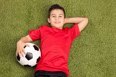 stock photo of football pitch  - Relaxed youngster in a red football jersey lying on a pitch - JPG