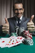 stock photo of won  - Royal FlushBusinessman Won In Poker Game And Show Thumbs Up - JPG