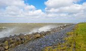 foto of dike  - Storm raging over a lake along a dike in spring - JPG
